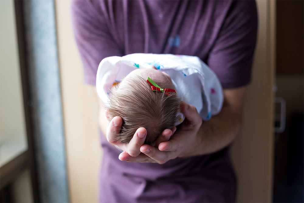 the cost of having a baby. cost of a baby. cost of having a baby. Image of a mom holding a newborn baby.