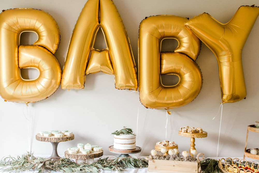 Classy decorated room with gold balloons spelling out BABY used to represent our baby shower planning page. Baby Shower Planning. Planning a baby shower. Baby Shower Tips.
