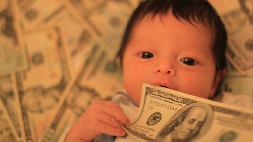An image of a baby laying on money representing BabyBety's article 10 Reasons To Start An Online Baby Pool.